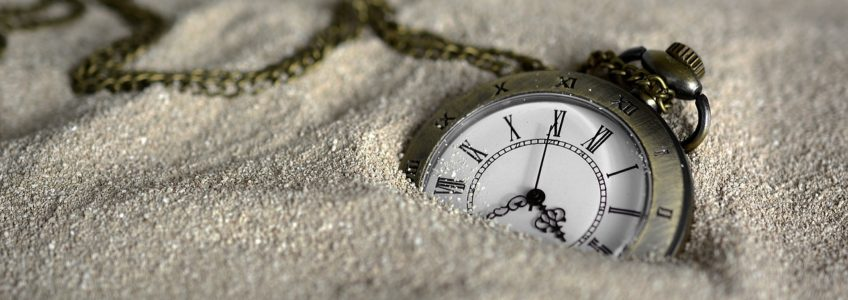 A watch half-buried in sand